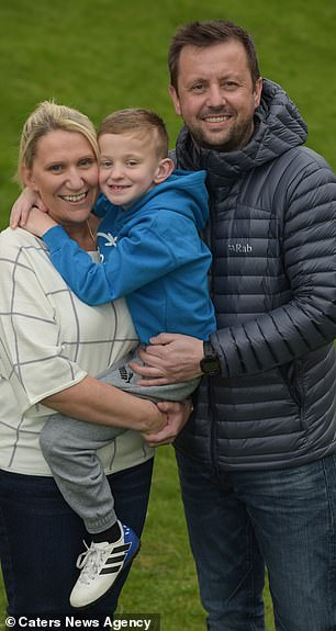 Tommy Plantdied for 15 minutes after having a sudden cardiac arrest and only survived due to his father's CPR skills. The seven-year-old is pictured after the ordeal with his parentsJason and Alison Plant