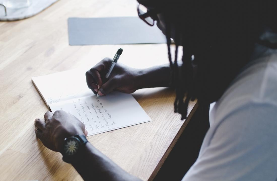 Man writing in journal, diary, or log.