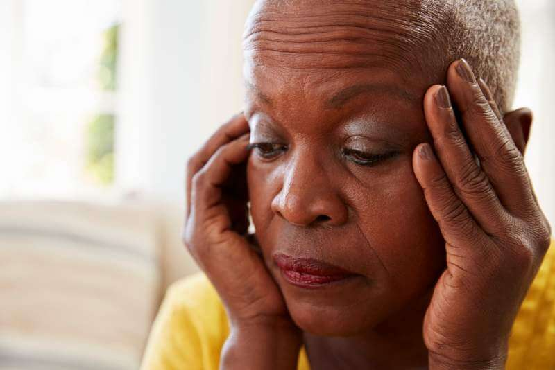 senior-woman-sitting-on-sofa-at-home-suffering