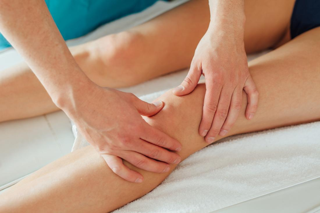therapist examining patients knee