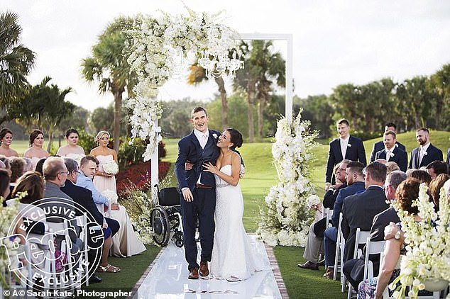 Beautiful moment: Chris trained for seven years to walk seven yards after they exchanged vows at a ceremony in Jupiter, Florida last year, supported by Emily the whole way