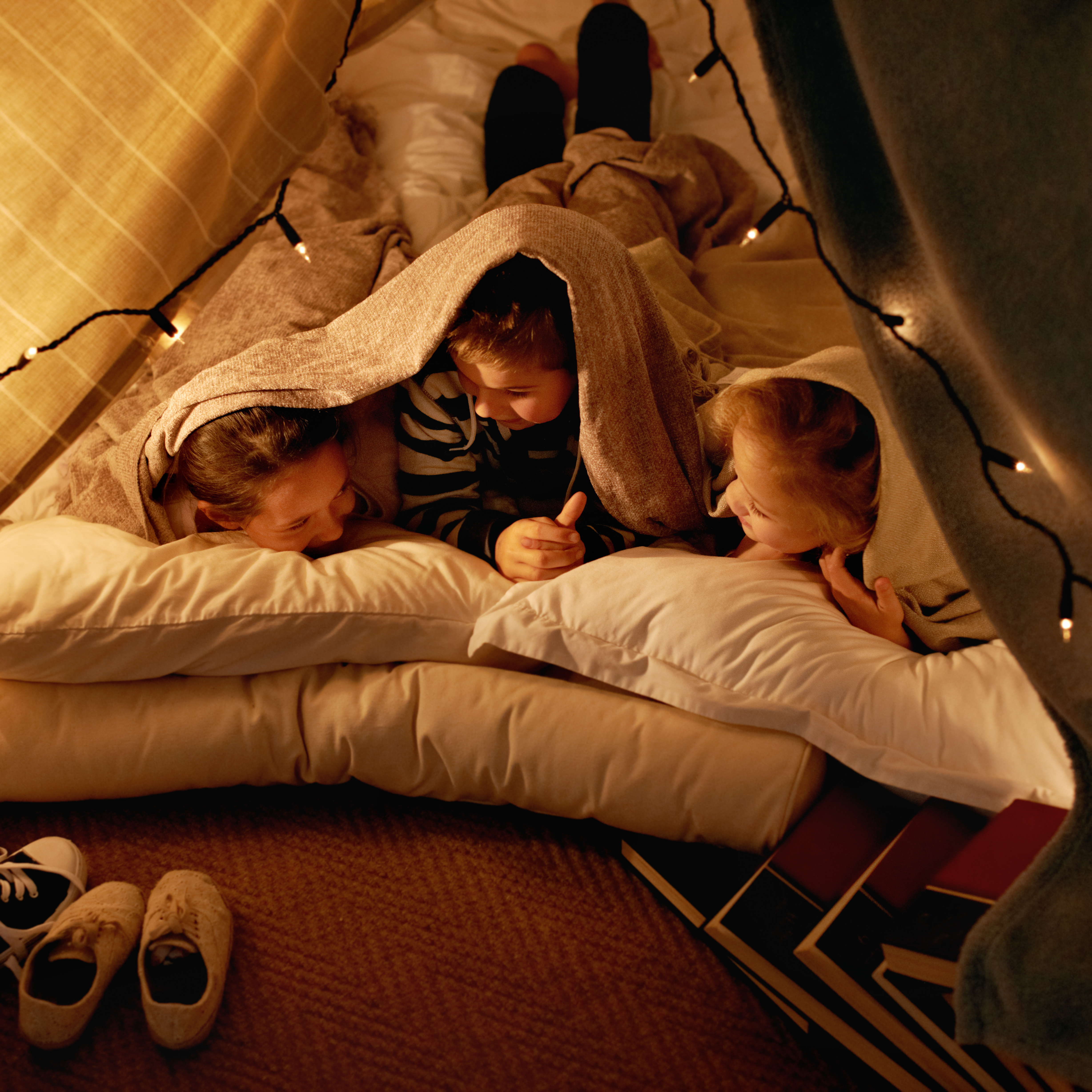 Children playing in blanket and pillow tent