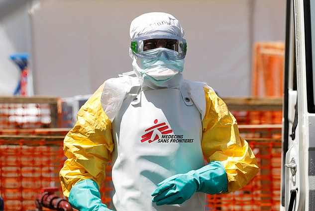 A worker in protective gear disinfects an ambulance carrying a suspected Ebola patient in DR Congo, amid claims that responses to epidemics so far have been 'grossly insufficient'