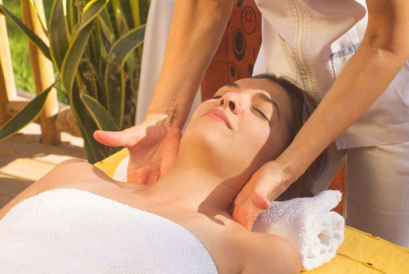 a-woman-lying-down-receiving-a-massage-from-a-professional-masseuse