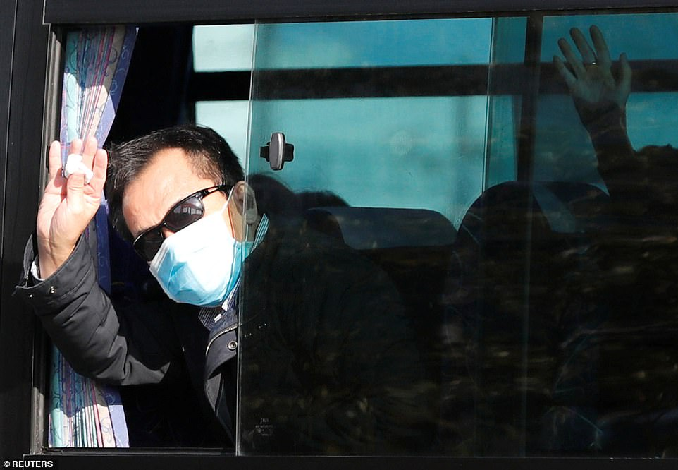 Passengers wave from a bus transporting Hong Kong passengers from the coronavirus-hit cruise ship Diamond Princess