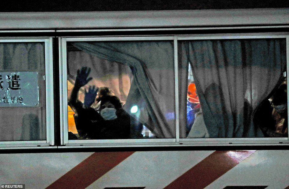 British passengers wave from the window of the bus after they left the coronavirus-hit cruise ship off Japan after being stranded for almost 20 days