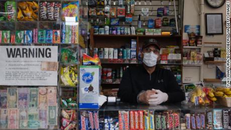 A worker wears a protective mask and gloves Wednesday at a deli in New Rochelle.