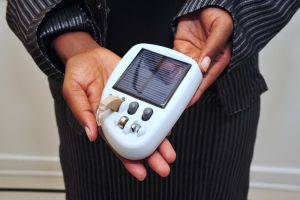 A solar hearing aid on its charger