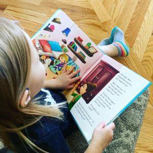 A little girl reading a book.